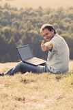 Young man using laptop. Sitting on the grass on the hillside Royalty Free Stock Images