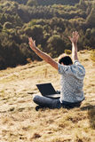 Young man using laptop. Sitting on the grass on the hillside Stock Photography