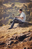 Young man using laptop. Sitting on the grass on the hillside Royalty Free Stock Photos