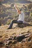 Young man using laptop. Sitting on the grass on the hillside Royalty Free Stock Photography