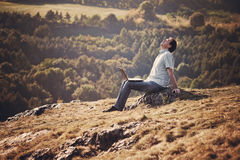 Young man using laptop. Sitting on the grass on the hillside Stock Photos