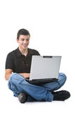 Young Man Using a Laptop. Young man sitting on the floor using a laptop. Isolated on white background Stock Photos