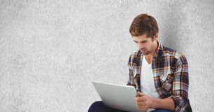 Young man using laptop against wall. Digital composite of Young man using laptop against wall Royalty Free Stock Photos