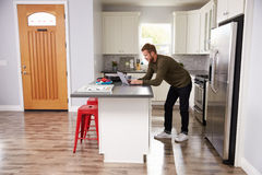 Young Man Using Laptop In Apartment Kitchen Royalty Free Stock Photography