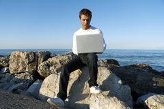 Young man using laptop at beach Royalty Free Stock Images