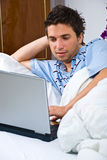 Young man using laptop in bed Royalty Free Stock Photography