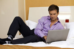 Young man using laptop on bed Stock Photography
