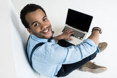 Young man using laptop with blank screen and smiling at camera Royalty Free Stock Photos