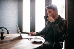 Young man using laptop at cafe Royalty Free Stock Photo