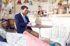 Young man using laptop at a cafe Stock Image