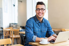 Young man using laptop at cafe Royalty Free Stock Image
