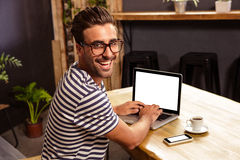 Young man using laptop in cafeteria Stock Image