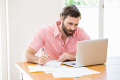 Young man using laptop while calculating a bills Stock Image