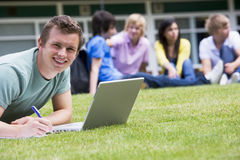Young man using laptop on campus lawn Royalty Free Stock Photo