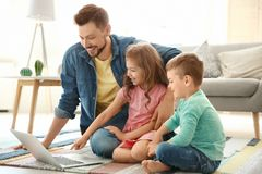 Young man using laptop with children at home. Young men using laptop with children at home. Happy family Stock Image
