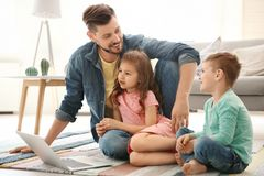 Young man using laptop with children at home. Young men using laptop with children at home. Happy family Royalty Free Stock Images