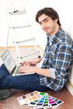 Young man using laptop while choosing color of his flat Stock Photo
