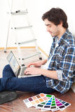 Young man using laptop while choosing color of his flat Stock Photography