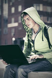 Young man using laptop on city street Royalty Free Stock Image