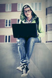 Young man using laptop on city street. Young man in a hood using laptop on city street Stock Image