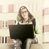 Young man using laptop in city street. Young man in a hoodie using laptop in city street Stock Image