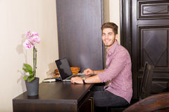 Young man using a laptop computer in a asian styled hotel room. A young and handsome man using a laptop computer in a asian styled hotel room Royalty Free Stock Images