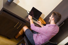 Young man using a laptop computer in a asian styled hotel room. A young and handsome man using a laptop computer in a asian styled hotel room Stock Photo