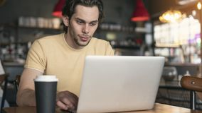 Young man using laptop computer in cafe stock photo