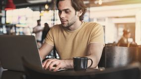 Young man using laptop computer in cafe royalty free stock image