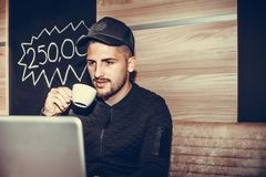 Young man using laptop computer and drinking coffee. Happy young man using laptop computer, drinking coffee  listening music and internet browsing at the cafe Stock Images