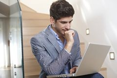 Young man using laptop computer at home. Young businessman sitting on stairs at home, using laptop computer, working Stock Images