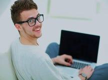 Young man using laptop computer at home. Looking at camera Stock Photos