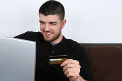 Young man using laptop computer for internet shopping Royalty Free Stock Photos