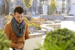 Young man using laptop computer outdoors. Young man sitting in citypark, using laptop computer Stock Images