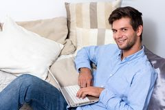 Young man using laptop on couch Royalty Free Stock Images