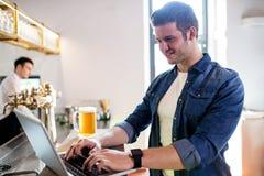 Young man using laptop at counter royalty free stock image