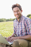 Young man using laptop in the countryside Stock Images