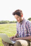 Young man using laptop in the countryside Royalty Free Stock Photography