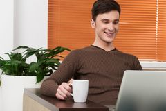 Young man using laptop and drinking tea. Royalty Free Stock Photos