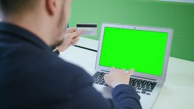 A Young Man Using a Laptop with a Green Screen stock images