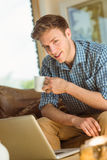Young man using laptop on his couch Royalty Free Stock Images
