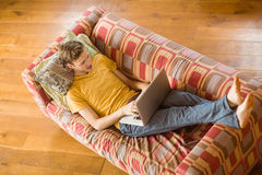 Young man using laptop on his couch Royalty Free Stock Image