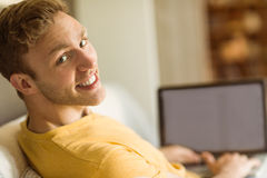 Young man using laptop on his couch Royalty Free Stock Photo