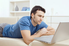 Young man using laptop at home Royalty Free Stock Photography