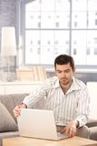 Young man using laptop at home sitting on sofa Royalty Free Stock Photos