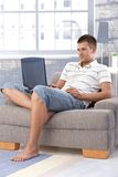Young man using laptop at home smiling Royalty Free Stock Photography