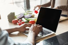 Young man working using laptop in the kitchen. Young man using laptop in kitchen while woman cooking dinner, closeup Royalty Free Stock Images