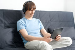 Young man using a laptop and listening music Royalty Free Stock Photos