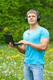Young man using a laptop and listening music Stock Photography