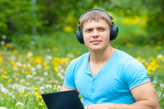Young man using a laptop and listening music Stock Images